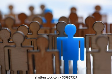 Figurine blue man in the crowd of wooden figures of ordinary people stands out from the rally as leader leader massone moves society politician special advantageous difference