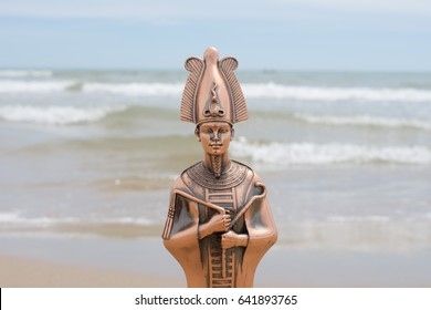 Figurine of the Egyptian God of Osiris against the background of the sea