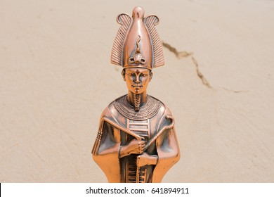 Figurine of the Egyptian God Osiris against the background of sand