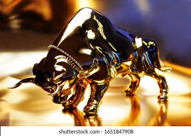 Figurine of a golden bull on a shining background. Golden bull figurine on a gold background. The golden calf is a symbol of profit, power, money, wealth.