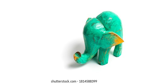 Figurine of a green wooden elephant with gilding isolated on white background. Decorative figurine of an elephant, hand carved wooden model of an elephant. Statuette, toy, souvenir from Asia