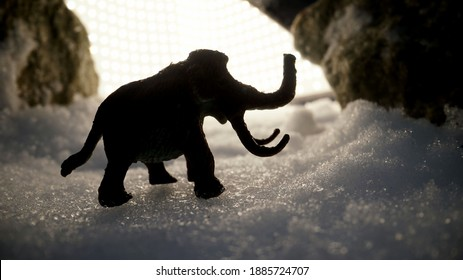 Figurine of a mammoth in a snowy landscape. Mammoth, mammoth frozen in ice. Mammoth on a background of ice.
