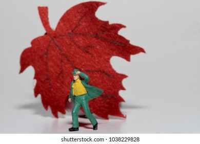 figurine miniature of a man walking against the wind with a fall leaf on the background