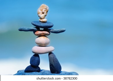 Figurine of pebbles on the against background the blue sky