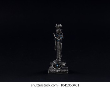 a figurine of a pharaoh on a black background