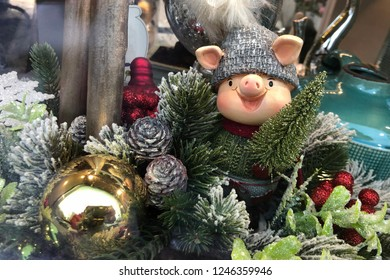 figurine of smiling pig in hat among Christmas tree toys decorations. 2019 new year of pig by Chinese horoscope, piglet toy symbol with Christmas tree bumps