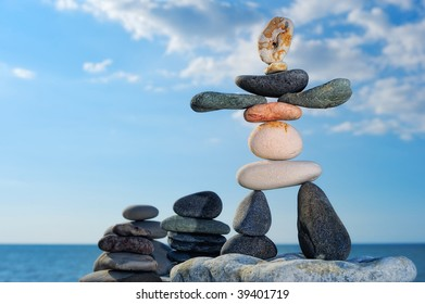 Figurine and stacked piles of black pebbles on the against the blue sky