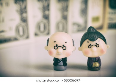 Figurines of an elderly couple on a background of money. vignetting.