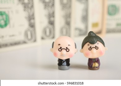 Figurines of an elderly couple on a background of money