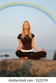 fiit girl meditating at the seashore under rainbow