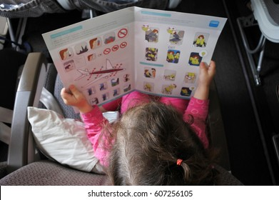 FIJI - DEC 11 2016:Little girl (Naomi Ben-Ari age 3) reads the safety information card during a flight. The odds of being killed on a single airline flight is 1 in 29.4 million