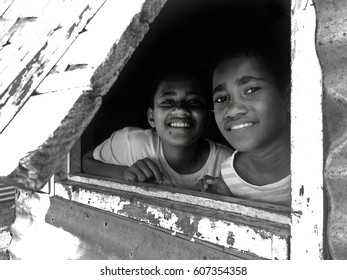 FIJI - DEC 25 2016:Young Indigenous Fijian people looks outside their home window.Indigenous Fijians are the indigenous people of Fiji Islands arrived from western Melanesia about 3,500 years ago
