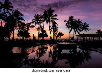 Fiji at Dusk. Silhouettes of palm trees reflected in a pool. Mauve and orange sky.