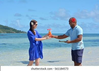 Fijian male waiter serving a tropical cocktail drink to a tourist woman in a resort on an island in Fiji. Travel holiday vacation concept. Real people copy space