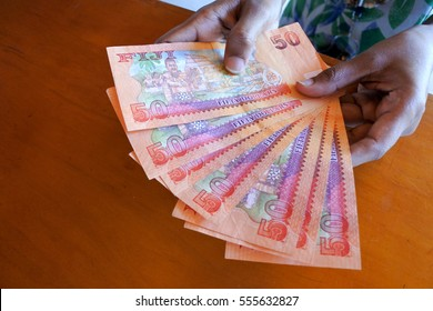 Fijian person counts 50 Fijian dollar bank notes over a wooden counter.