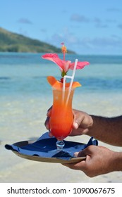 Fijian waiter serving red cocktail with red Hibiscus flower on a beach of a resort on the Yasawa Islands Fiji. Copy space