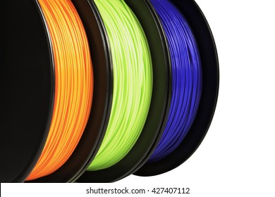 Filament for 3d printing. Bright thermoplastic of neon orange, green and blue colors. Isolated on white background. Material produced from poly-lactic (pla) acid. Three reels vertical view. Macro