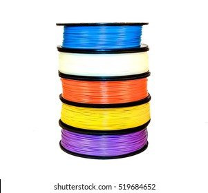 Filament for 3d printing: five coils of thermoplastic. The bright blue, white, orange, yellow and lilac colors. Isolated on white background. Material is Acrylonitrile butadiene styrene (ABS) polymer.