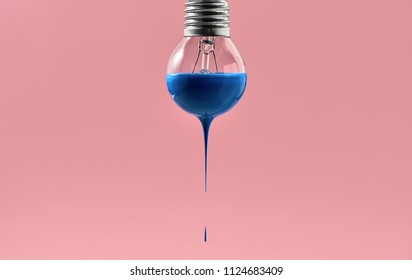 Filament bulb with blue paint on the pink background in the studio. Paint is dripping down from it. Closeup. Horizontal.