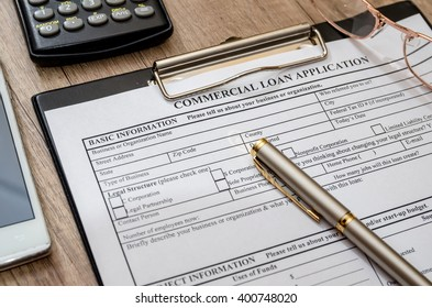 File the commercial loan application with calculator, pen on desk