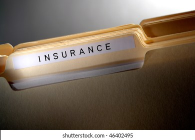 File folder for casualty and risk coverage policy papers in a stack of household documents with insurance title tab