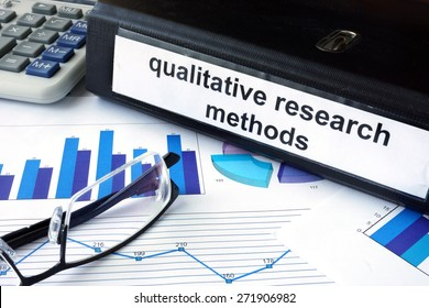 File folder with words words qualitative research methods and financial graphs. Business concept