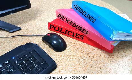 Files with label guidelines, procedures and policies on a table.