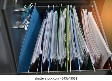 Files placed on a metal filing cabinet.