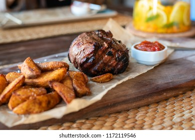 Filet Mignon with fried potatoes and tomato sauce on a wooden Board with Cutlery.