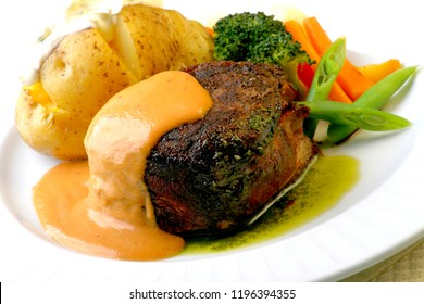 Filet mignon with mustard sauce accompanied by baked potato, carrot and broccoli.