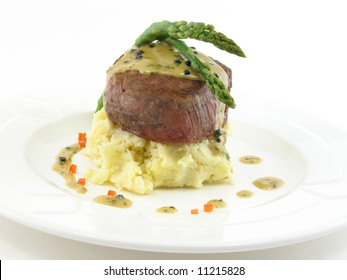 Filet mignon over mashed potatoes with asparagus on a white plate isolated on white.