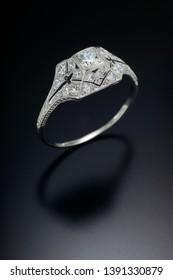 A filigree style antique diamond engagement ring with a one carat center stone and surrounded by  accent side diamonds set in platinum.