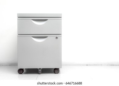 Filing cabinet standing on white wall