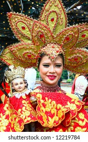 filipina girl in costume carrying an image of the child Jesus