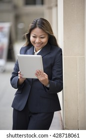 Filipino businesswoman outside in modern city using a digital tablet PC.