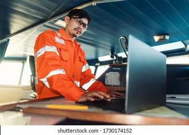 Filipino deck Officer on bridge of vessel or ship wearing coverall during navigaton watch at sea . He is using laptop, electronic paperwork at sea, concept of reporting