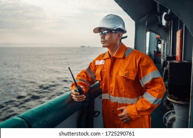 Filipino deck Officer on deck of vessel or ship , wearing PPE personal protective equipment. He holds VHF walkie-talkie radio in hands. Dream work at sea