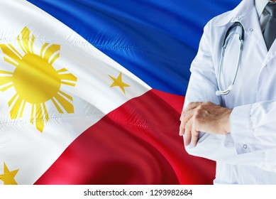 Filipino Doctor standing with stethoscope on Philippines flag background. National healthcare system concept, medical theme.