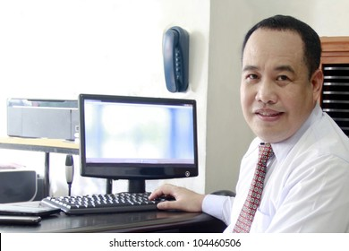 A Filipino executive in his office with business machine around.