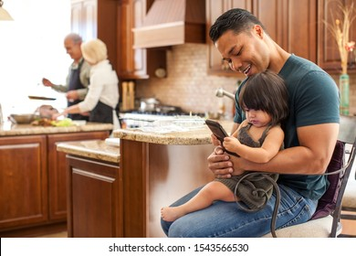 Filipino father with his baby girl looking at cell phone