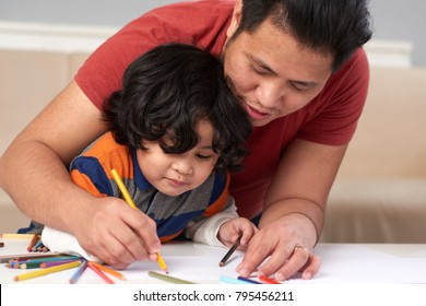 Filipino father and son drawing together