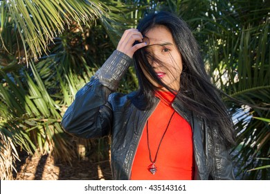 Filipino girl in a photo shoot in a city park on a sunny summer day. She is receding hair of the face that has been moved by the wind.