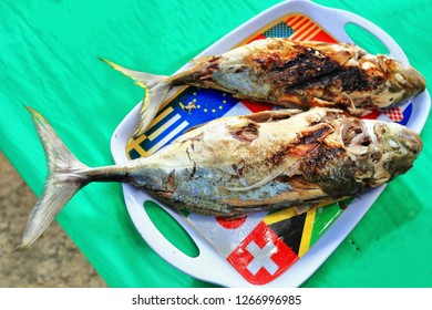 Filipino grilled seafood-torpedo or hardtail scad fish on a dish ornate with some national flags -Swiss-South African-Japanese-Greek-Croatian-American-. Cudugnon Cave beach-El Nido-Palawan-Philippines