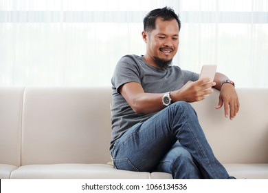 Filipino man sitting on sofa and reading messages in his phone