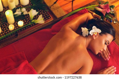 Filipino massage of woman in spa salon. Girl on candles background . Luxary interior in oriental therapy .