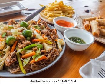 Filipino meal, Pancit Sotanghon, tuna spring rolls and French fries.