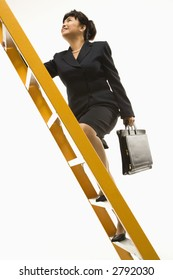 Filipino middle-aged businesswoman climbing ladder carrying briefcase.