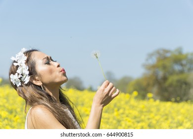 Filipino model trying to blow off the seeds of a gone to seed dandelion