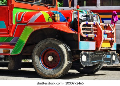 Filipino orange-red dyipni-jeepney car. Public transportation in Sagada town-originally made from US.military cars left over from WW.II locally altered-now from japanese surplus. Igorot-Philippines.