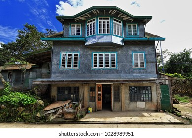 Filipino vernacular architecture-three storey grey cottage with tin roof and feed store on the ground floor by the South Road. Sagada town-Mountain province-Cordillera region-Luzon island-Philippines.